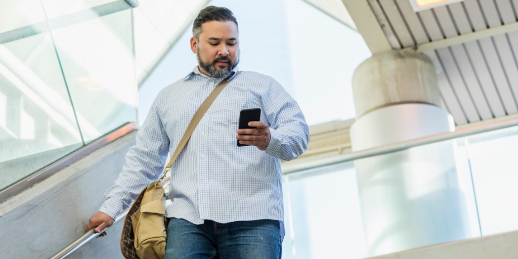 A man in his 30s wearing a button down shirt, walking down stairs outside a building, looking down at his mobile phone.