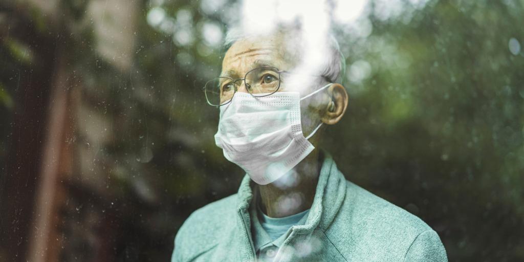 Senior man wearing mask looking through window.