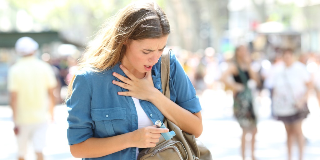 asthmatic-girl-suffering-an-attack-and-searching-inhaler-picture-id1030853356