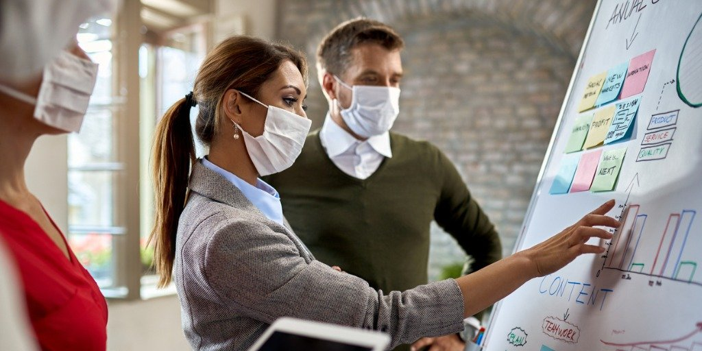 Businesswoman and her coworkers wearing protective face masks while making new business strategy on whiteboard during coronavirus epidemic.