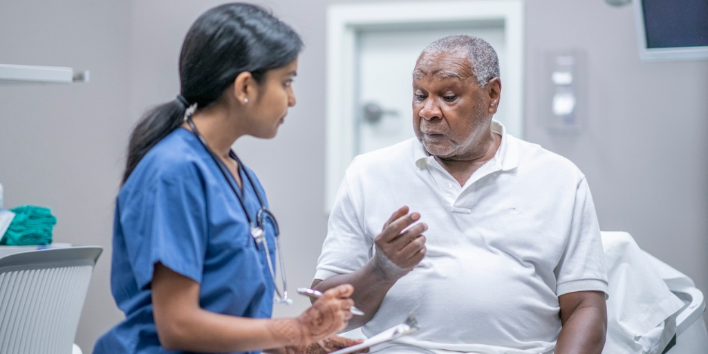 elderly-male-patient-talking-with-female-doctor-stock-photo-picture-id1212821220