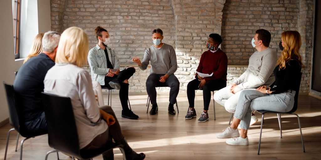 A group of individuals wearing masks sitting in a circle of chairs and talking.
