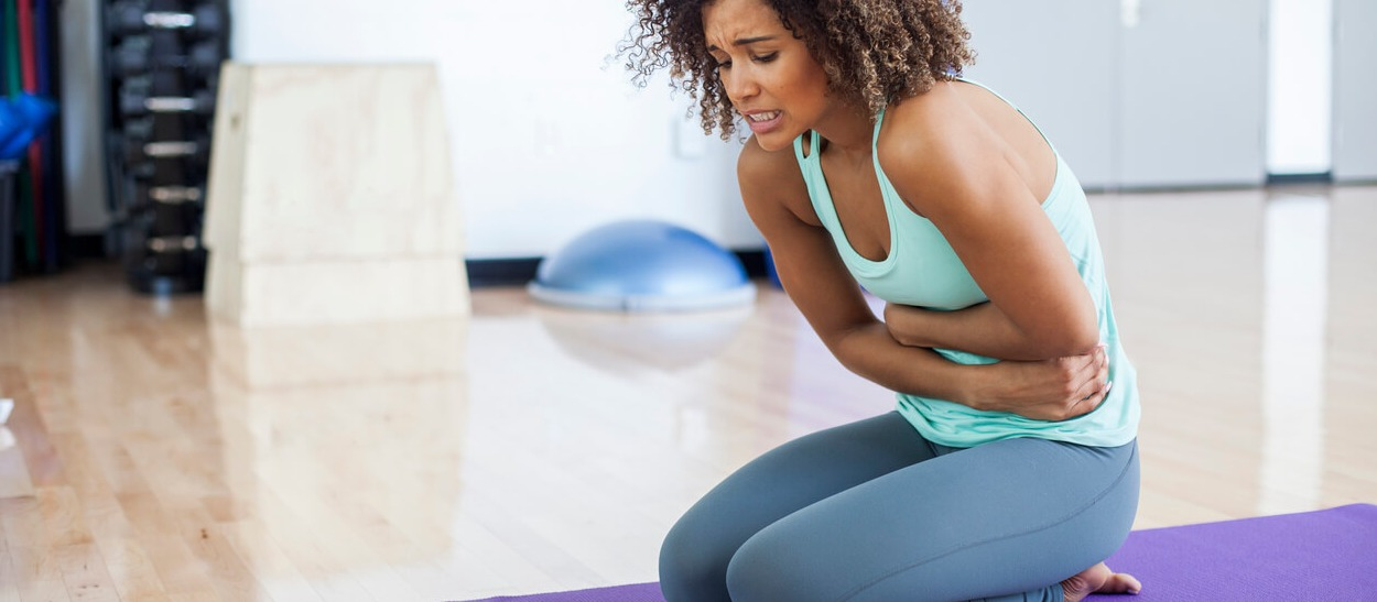 Yoga woman experiencing an ulcerative colitis flare while doing yoga.