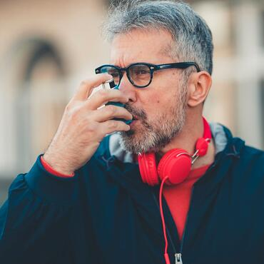 man-using-an-asthma-inhaler-picture-id1140574879