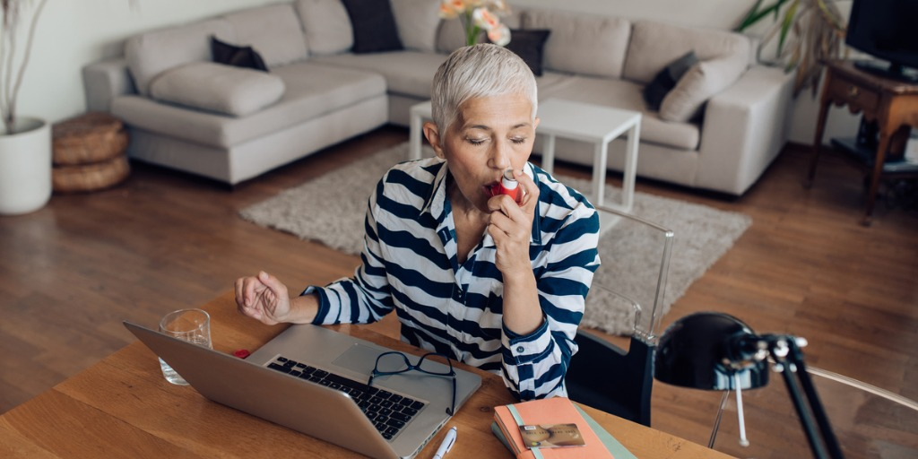 Mature woman using asthma inhaler while working on a laptop at home.
