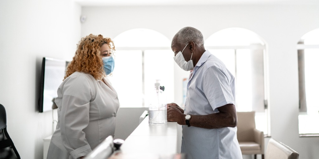 Medical clinic receptionist talking to patient