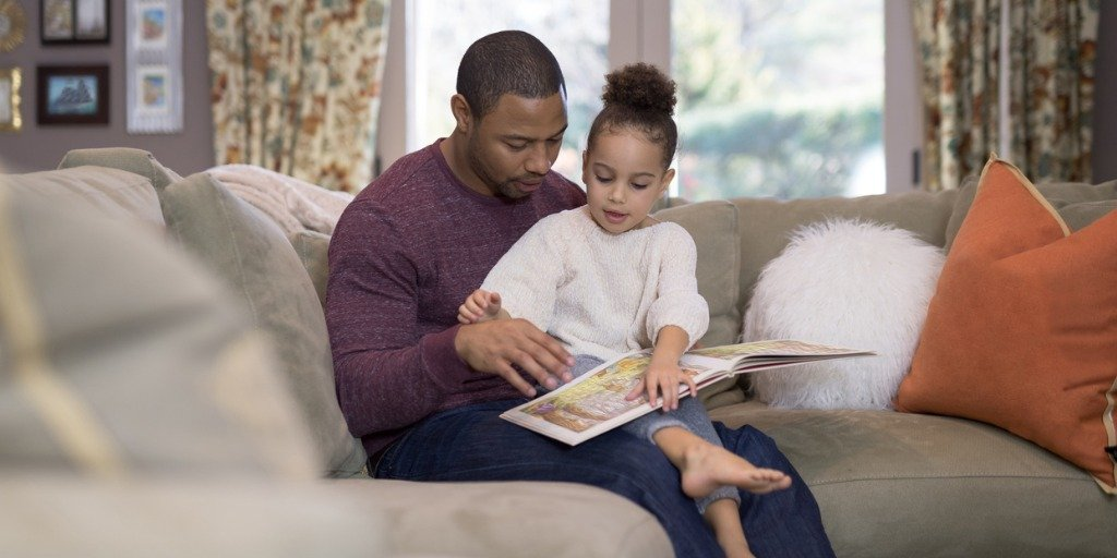 An African-American pre-school age girl sits on dad's lap in the living room and reads a book. She is pointing out her favorite parts and making sure he's not skipping any pages...
