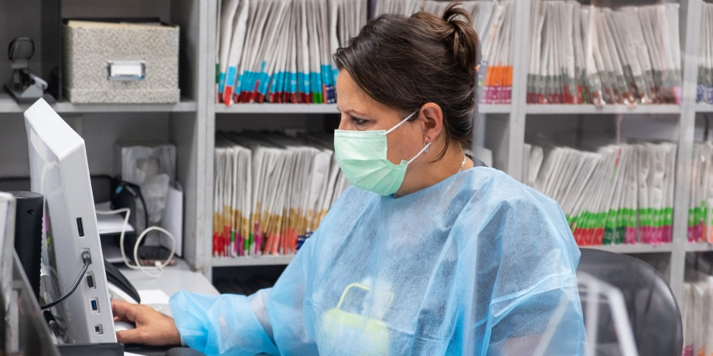Receptionist at medical office wearing mask and gown for protection during the Covid-19 pandemic. She is working at the computer with patient files in the background.