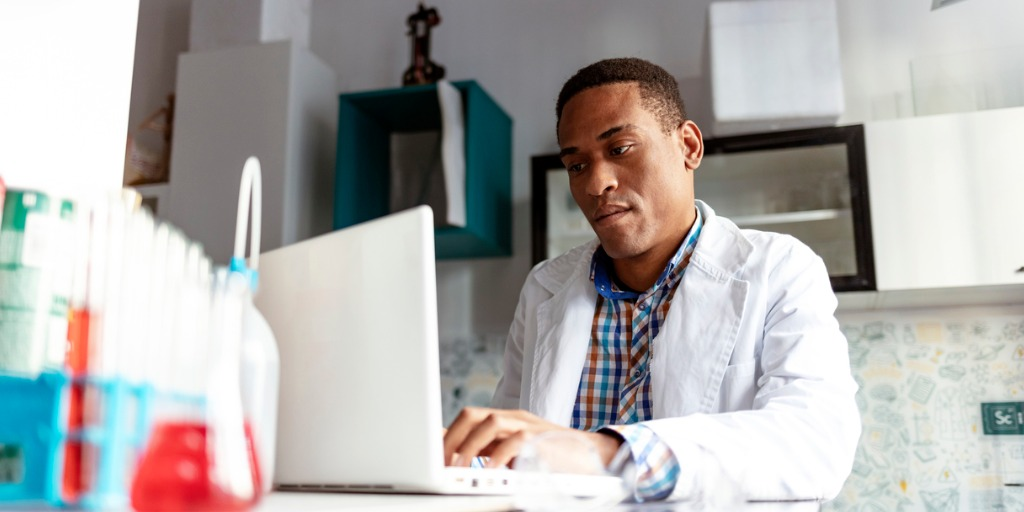 African-American Male scientist working in the laboratory with laptop
