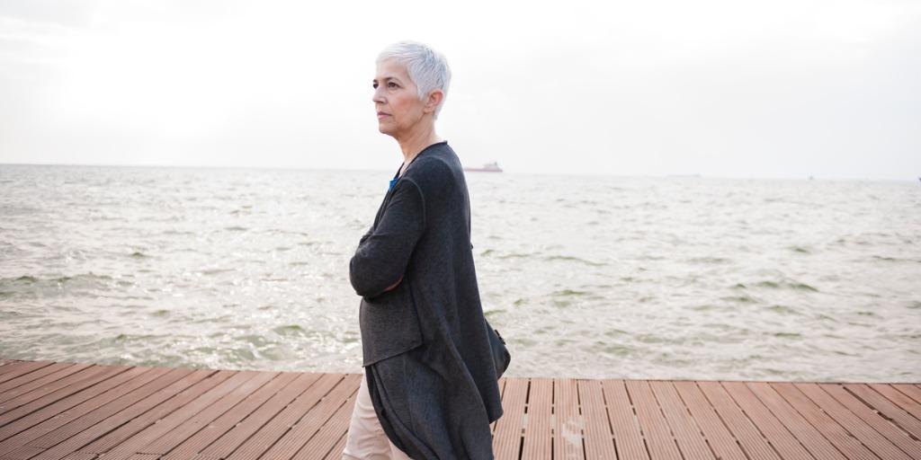 Mature business woman at coast, walking