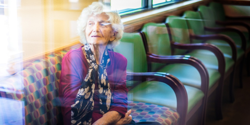 Senior woman sitting in a waiting room at a doctor's office.