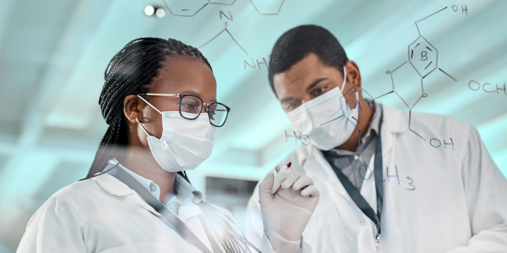 Two scientists drawing molecular structures on a glass wall in a lab