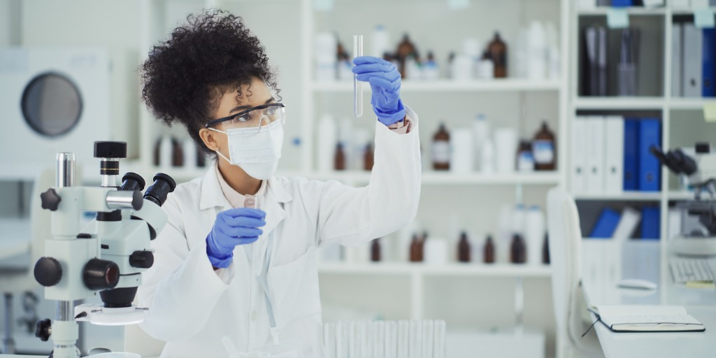Cropped shot of a young female scientist inspecting a liquid sample in a test tube while working in a laboratory