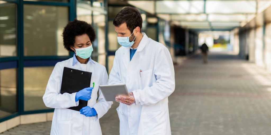 Two doctors looking at medical results on digital tablet in front of a hospital building.
