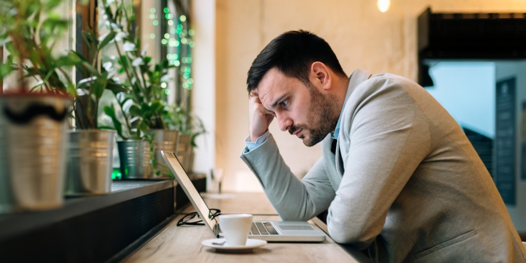 Worried man looking at laptop screen while sitting in an office cafe.
